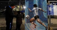 A banner with a painted image of Argentine soccer legend Diego Maradona is displayed as people gather to mourn his death outside San Paolo stadium in Naples, Italy November 25, 2020. REUTERS/Yara Nardi